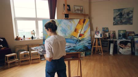 visual : Pan shot of serious girl professional painter working in studio painting marine landscape with tempera paints holding palette and brush. Artworks and creativity concept.