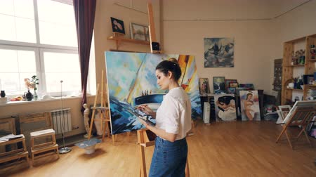 шедевр : Serious artist is working in workroom standing in front of easel with palette and brush and painting picture boat and sea waves in acrylic paints. People and hobby concept.