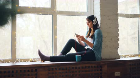 sill : Cute girl brunette is sitting on window sill, listening to music in headphones and using smartphone. Modern interiors, technology and relaxing people concept.