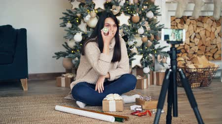 wrapping paper : Skillful girl creative vlogger is recording video about gift boxes and present wrapping sitting near decorated Christmas tree and using smartphone camera.