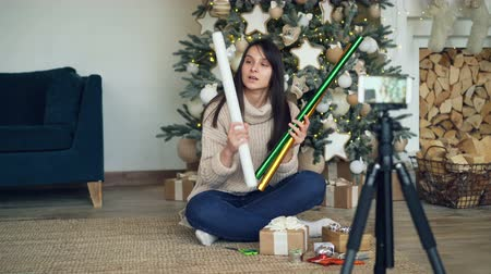 vlogging : Creative young lady is recording video for online vlog about gift-wrapping for Christmas holidays. Girl is showing wrapping paper, boxes, ribbons and scissors.
