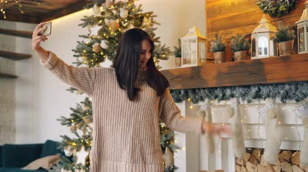 despreocupado : Beautiful girl is making online video call with smartphone on Christmas day standing near fireplace and fir-tree, talking and waving hand showing gift box.