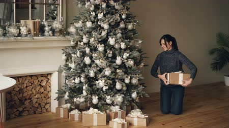 beautifully : Happy young lady is putting presents under beautifully decorated New Year tree then looking at gift boxes and smiling. Nice modern house with fireplace is visible.