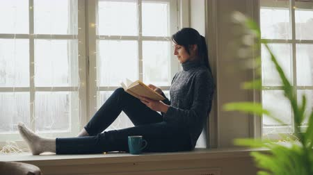 читатель : Pretty brunette in sweater and jeans is reading book sitting on window-sill on Christmas day enjoying soliture, free time and holiday. Literature and rest concept. Стоковые видеозаписи