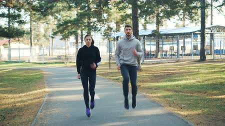 aerobic : Beautiful couple pretty girl and bearded guy are exercising in park together running and jumping. Active lifestyle, healthy youth and leisure concept. Wideo
