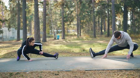 sportowiec : Young handsome man and female friend are training in park together stretching legs on warm autumn day wearing trendy tracksuits. People, sports and leisure concept. Wideo