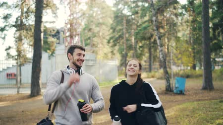 пять : Young handsome man in headphones is talking to his female friend and laughing walking in park with sports bags after outdoor training then doing high-five.