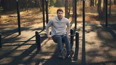 bodyweight : Young sportsman is doing sports outdoors in park sports-ground working at arm and leg muscles and abs using metal bars. Fitness, youth and nature concept. Stock Footage