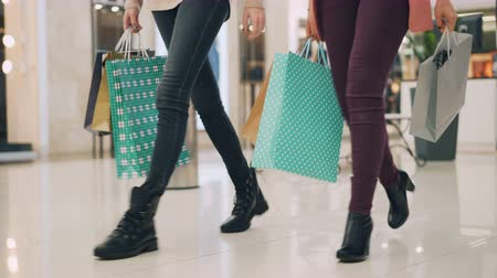 denim : Female friends students are walking in shopping mall holding paper bags in hands enjoying season sale. Womens legs, light store interior and clothing are visible. Stock Footage