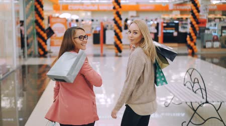 pátek : Slow motion of cheerful young ladies happy customers walking together in shopping mall holding colorful bags then turning to camera and smiling. Shopaholics and shops concept. Dostupné videozáznamy