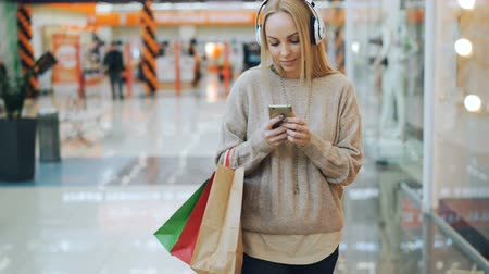 iyi bir ruh hali : Happy young woman with long blond hair is listening to music through headphones and using smartphone while walking in shopping mall with paper bags. Stok Video