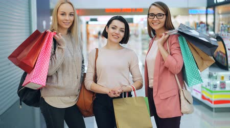espetacular : Portrait of happy girls shoppers with colorful paper bags standing together in shopping mall looking at camera and smiling. Youth lifestyle and shops concept. Stock Footage
