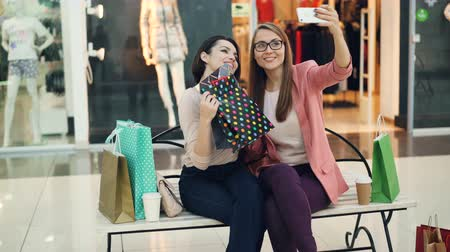 bolsa de compras : Cute girls are taking selfie in shopping mall posing with paper bags and trendy hand gestures sitting on bench in boutique. Women are having fun and laughing.