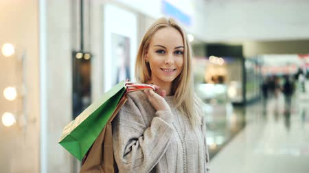 duyarlı : Portrait of good-looking lady with long blond hair looking at camera and smiling standing in shopping mall with paper bags. Moder youth and buying things concept. Stok Video