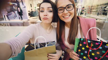 язык : Point of view shot of young women students taking selfie in shopping mall showing bright paper bags and thumbs-up and making funny faces. Shopaholics and joy concept.