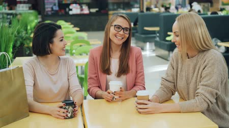 tea bag : Group of happy young ladies is chatting and laughing sitting at table in shopping mall cafe with to-go drinks and socializing. Youth lifestyle and fun concept.