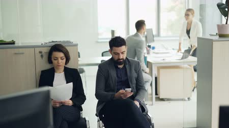 kandidát : Young people man and woman are waiting for job interview in office while manager is interviewing another candidate. Girl is holding cv, guy is using smartphone.