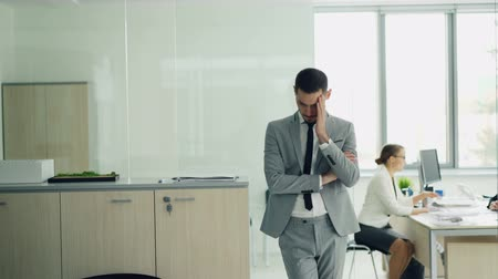 recrutamento : Stressed young man in suit is standing in office waiting for job interview while female interviewer is talking to another candidate. Emotions and employment concept.