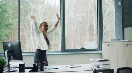 victorious : Female office worker is talking on mobile phone then dancing and yelling throwing papers celebrating good news. Success, emotions and youth concept. Stock Footage