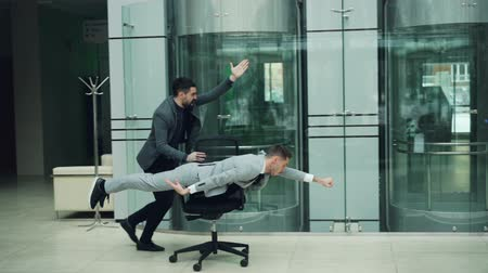 lobby : Bearded guys businessmen are having great time at office party riding chair in lobby enjoying freedom amd good mood. Funny adults and workspace concept. Stock Footage