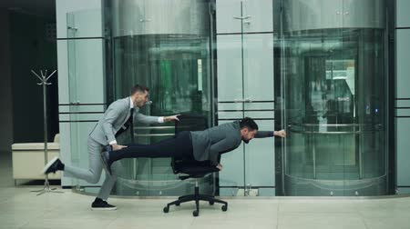 стулья : Joyful office workers are having fun with rolling chair in lobby of business center riding armchair and laughing enjoying funny activity at work party.