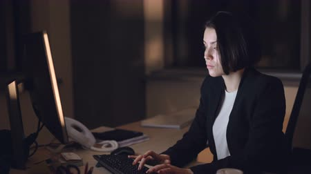 dedicado : Businesswoman in formal suit is working on computer night shift sitting at desk typing and looking at screen. Busy young people, overwork and career concept.