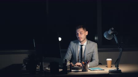 stres : Tired young man in suit is working on computer late at night sitting in office alone finishing job rubbing his face having headache. Overwork and youth concept.