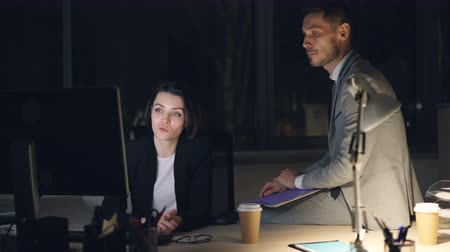 dedicado : Serious businesspeople man and woman in suits are working together in dark office late at night looking at pc screen and talking discussing job issues.