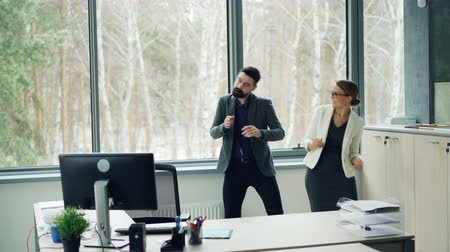 victorious : Good-looking young people coworkers are dancing in office and clapping hands enjoying music and relaxation. Youth lifestyle, job and partying concept.