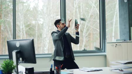 carelessness : Excited young businessman is counting cash in office then throwing money in air and dancing expressing positive emotions. Freedom, youth and finance concept. Stock Footage