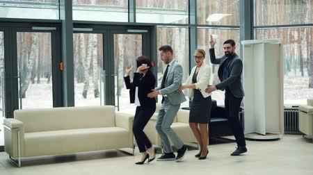 baví : Good-looking men and women business people are dancing in lobby together laughing and having fun at corporate party. Coworkers, emotions and millennials concept.