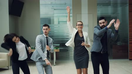 партнеры : Happy business team men and women are dancing at work party together moving bodies, laughing and singing relaxing in hall. Coworkers, relaxation and emotions concept.