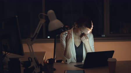 kariyer : Exhausted young lady is working in office late at night using laptop then taking off her glasses and rubbing face relaxing. Overwork and millennials concept.