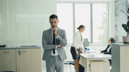 toborzás : Nervous young man in smart suit is waiting for job interview in modern office then walking inside and starts talking to interviewer. Stress and youth concept. Stock mozgókép