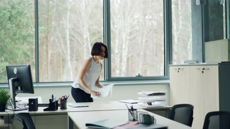 enjoyable : Happy young woman is dancing in office taking off jacket and throwing papers tossing her hair enjoying freedom and good mood. Corporate fun and youth concept. Stock Footage