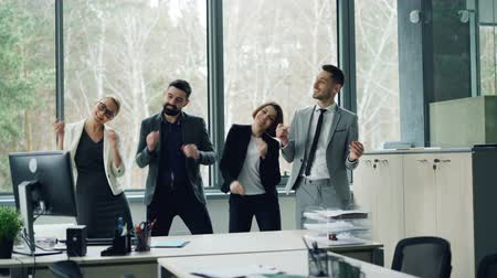партнеры : Group of happy carefree coworkers is dancing in office celebrating company event at party, laughing and having fun. Youth, job and emotions concept.