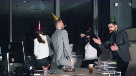 veselí : Happy young people office workers are dancing at company party wearing party hats and blowing horns. Birthday cake and gift box are visible on desk. Dostupné videozáznamy
