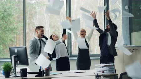 crazy girl : Group of cheerful colleagues is dancing in office celebrating company event at party, throwing papers, laughing and having fun. Youth, job and emotions concept.