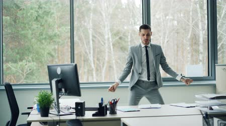 oblek : Good-looking bearded man in suit is dancing in office room alone moving body and arms then taking papers from desk and throwing them on floor. Joy and emotions concept.