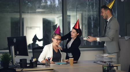 congratulating : Pretty blonde is working in modern office when her colleagues are bringing birthday cake, present and party hats, girl is opening gift box and enjoying congratulations