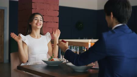 bűbájos : Loving young man is making proposal to his girlfriend in restaurant, girl is saying yes, boyfriend is giving her engagement ring and kissing hand. Marriage and dating concept.