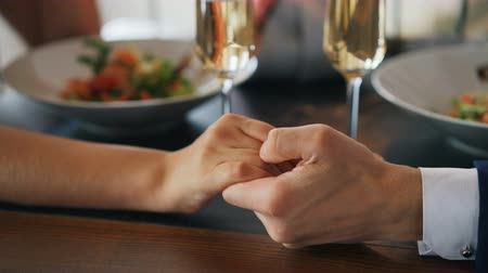 nişanlısı : Close-up shot of two hands male and female on table with sparkling champagne glasses and plates with food. Romance, young love and restaurants concept. Stok Video