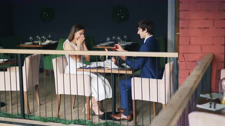 bűbájos : Beautiful couple man and woman are enjoying date in restaurant when guy is making marriage proposal to girl, giving her engagement ring and kissing hand. Stock mozgókép