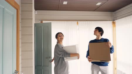 coming home : Happy couple bringing boxes with personal things after relocation to new house, looking around, smiling and kissing. Moving to new home and relationship concept.