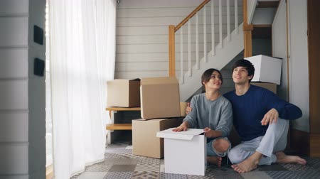 tehcir : Young people husband and wife are talking and kissing sitting on floor of new house near staircase and dreaming making plans about life in new home. Relocation and youth concept.