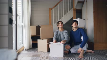 宿泊施設 : Attractive young woman loving girlfriend is talking to her boyfriend then giving him house keys sitting on floor of new apartment. Relocation and moving in concept.