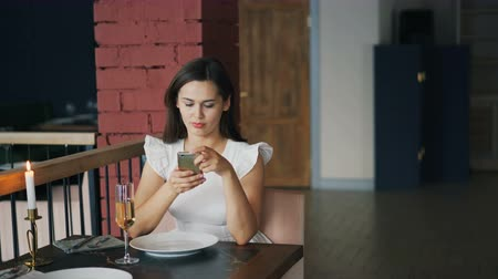 unalom : Attractive young woman in beautiful dress is waiting for her boyfriend in restaurant sitting at table alone and using smartphone checking time. Dating and technology concept.
