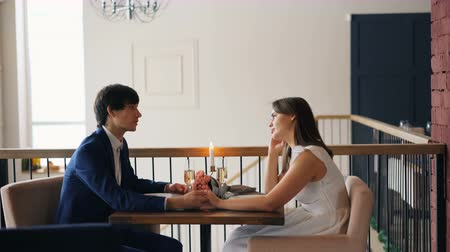 заботливый : Happy young people girl and guy are talking holding hands sitting at table with flowers, candles and champagne in nice restaurant. Dating and conversation concept.