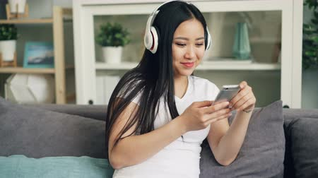 enjoyable : Asian young lady with beautiful long black hair is listening to music through headphones and using smartphone enjoying leisure time at home. Youth and technology concept.