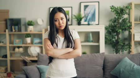 expressing negativity : Portrait of angry Asian lady looking at camera, frowning and shaking her head expressing disappointment and disapproval standing with arms crossed at home. Stock Footage